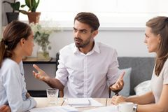 Angry businessman arguing with female subordinate at group business meeting. Angry businessman arguing with female subordinate at group meeting. Dissatisfied stock images