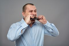 Angry businessman biting his cellphone. Angry business man biting his cellphone on gray background Stock Photography