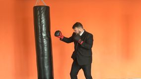 Angry businessman in black suit relieves stress in fitness club. Manager or boss in boxing gloves beats punching bag in stock video