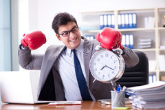 The angry businessman with boxing gloves in time management concept Stock Photo