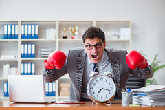 The angry businessman with boxing gloves in time management concept Royalty Free Stock Photo