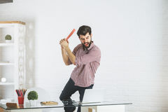 Angry businessman breaking laptop Royalty Free Stock Photos