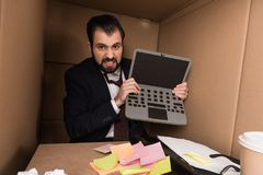 Angry businessman with cardboard laptop. Angry businessman holding cardboard laptop in box Royalty Free Stock Image