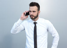 Angry businessman at the cell phone. Angry businessman talking on the cell phone Royalty Free Stock Photography