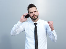 Angry businessman at the cell phone. Angry businessman talking on the cell phone Stock Photo
