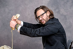 Angry businessman is choking his phone Stock Photo
