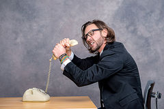 Angry businessman is choking his phone Stock Photos