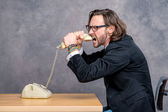 Angry businessman is choking his phone Royalty Free Stock Photo
