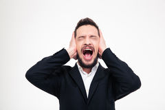 Angry businessman covering his ears and screaming Stock Photos