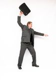 Angry businessman ejecting briefcase. Stock Image