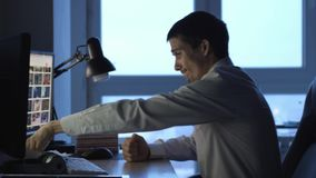Angry businessman in formalwear working on computer in office at night, then throws papers. 3840x2160 stock footage