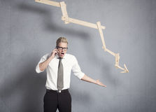 Angry businessman in front of graph pointing down. Royalty Free Stock Image