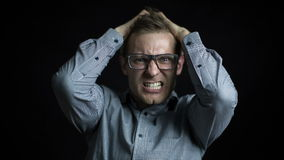 Angry businessman with glasses shouting isolated in a black background Stock Photos