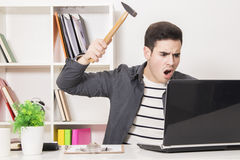 Angry businessman with hammer. An angry businessman holding a hammer aiming at the laptop in front of him Stock Image
