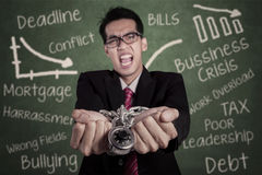 Angry businessman with hands chained at class Stock Image