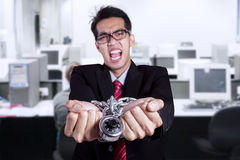 Angry businessman with hands chained at office Royalty Free Stock Image