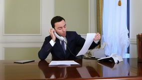 Angry businessman has a heated conversation with someone on landline phone stock video