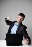 Angry businessman hitting his laptop. Angry businessman hitting hit laptop with fist Royalty Free Stock Images