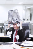 Angry businessman hold rubbish bin on his head at office Royalty Free Stock Photos