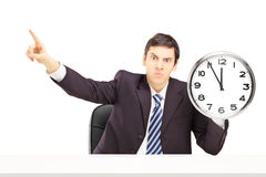 Angry businessman holding a clock and gesturing with his finger Royalty Free Stock Photo