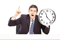 Angry businessman holding a clock Royalty Free Stock Image