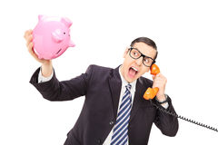 Angry businessman holding an empty piggybank Stock Images