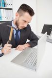 Angry businessman holding hammer over laptop Royalty Free Stock Photo