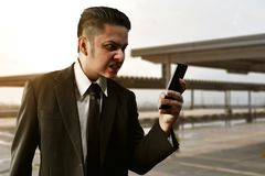 Angry businessman holding mobile phone. Angry business man holding phone Royalty Free Stock Image