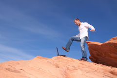 Angry businessman kicking his laptop. Young angry businessman kicking his laptop on the rocks Royalty Free Stock Image