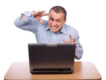 Angry businessman at laptop. Isolated on white Stock Photography