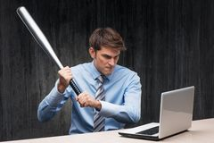 Angry businessman with laptop and bat. Angry businessman with laptop and throwing-stick. Computer hacker concept Royalty Free Stock Photography