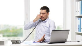 Angry businessman with laptop calling on phone stock video footage