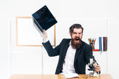 Angry businessman with laptop. Angry man businessman male scientist hipster with laptop and microscope shouts furiously in office with board for copy space on Royalty Free Stock Photo