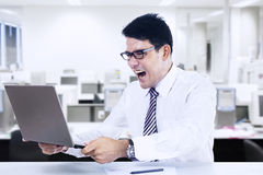 Angry Businessman. With a laptop in office Stock Photography