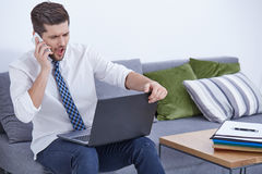 Angry businessman with laptop. And phone working at home Stock Photography