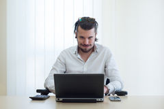 Angry businessman with laptop. Young businessman at work with laptop, worn-out Royalty Free Stock Photo