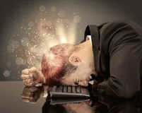 Angry businessman with lights and keyboard. A young depressed business person laying his head on computer keyboard with thoughts exploding from his head Stock Photos