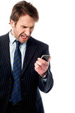 Angry businessman looking at his phone Royalty Free Stock Image