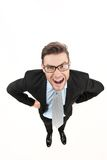 Angry businessman looking up and wearing glasses on white. Stock Photography