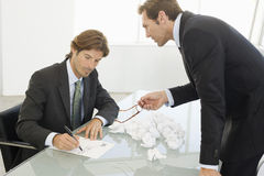 Angry Businessman With Male Colleague Writing On Paper Royalty Free Stock Image