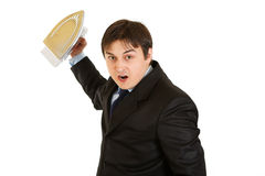 Angry businessman menacingly holding iron in hand Royalty Free Stock Image