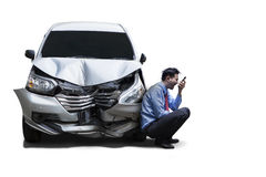 Angry businessman next to damaged car Royalty Free Stock Image