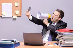 Angry businessman in an office. Shouting on a megaphone, holding a mobile phone in the hand royalty free stock photography