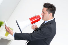 Angry businessman in an office, shouting on a megaphone, holding. A mobile phone in the hand Stock Images