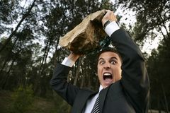 Angry businessman outdoor, big stone in hands. Angry businessman in outdoor forest, big stone in hands Stock Photos