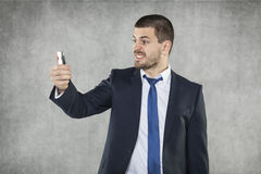 Angry businessman with a phone in his hand Royalty Free Stock Photo