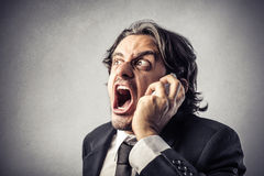 Angry businessman at the phone royalty free stock image