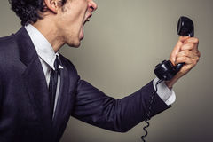 Angry businessman on the phone. An angry young businesman is on the phone and screaming Royalty Free Stock Image