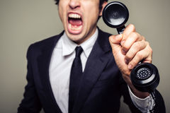 Angry businessman on the phone. An angry young businesman is on the phone and screaming stock photos