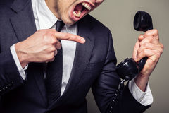 Angry businessman on the phone. An angry young businesman is on the phone and screaming Stock Photo